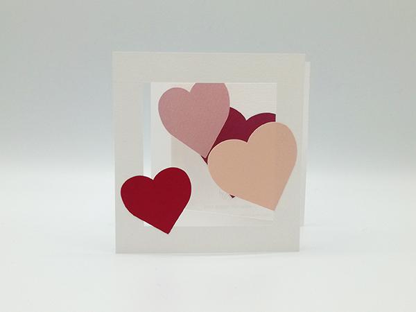 Carte avec pliage en accordéon, motifs cœurs rouges et roses, vue de face