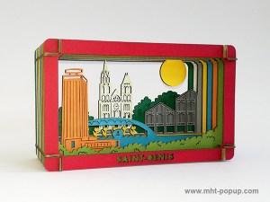 Diorama en couleur avec éléments du patrimoine de Saint-Denis (Basilique, canal, marché, tour Pleyel…), à monter soi-même. Vue de profil droit