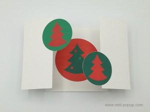 Carte de vœux à volets, vue de dessus carte ouverte sapins verts sur fond rouge et motif central inversé variante 1