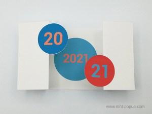 Carte de vœux à volets 2021, version violine-orange, vue dessus carte ouverte avec motif central bleu clair