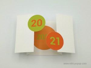 Carte de vœux à volets 2021, orange-vert, vue carte ouverte de dessus avec motif central orangé