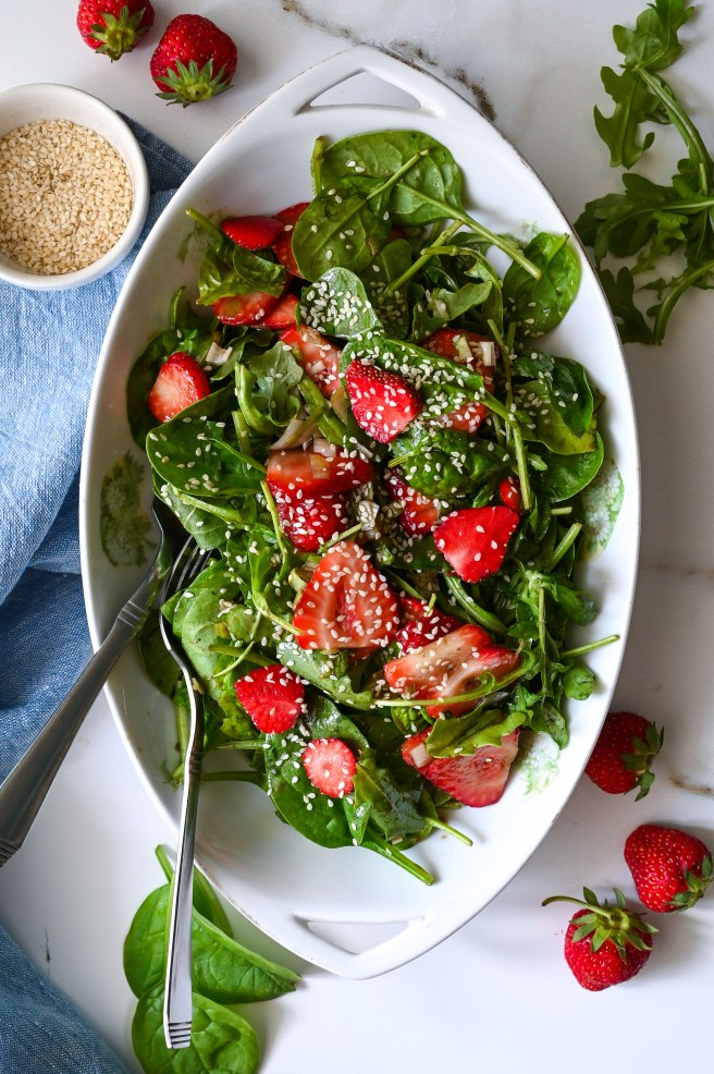 A delightful summer salad made with baby spinach, fresh strawberries and tossed with a slightly sweet vinaigrette