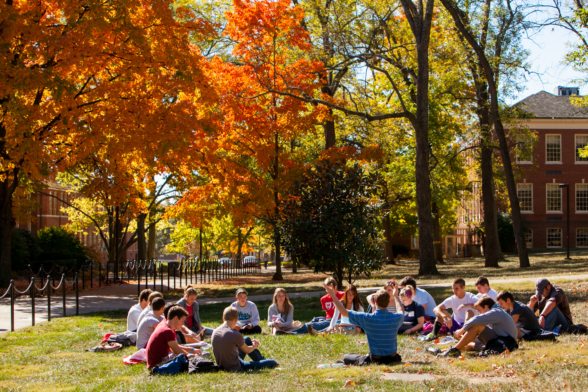 Students sitting on Miami University's campus in the fall
