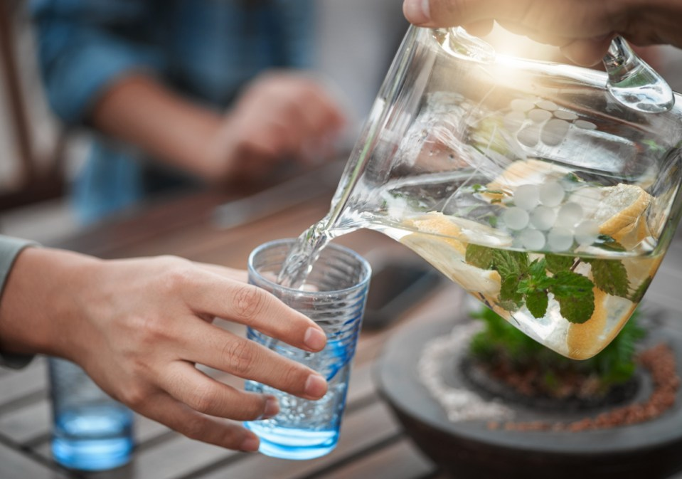 Shot of a unrecognizable person pouring water into a glass outside around a table
