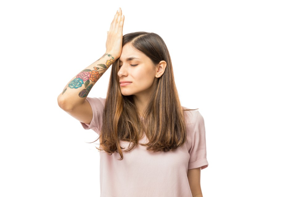 Woman realizing mistake and keeping hand on head over white background