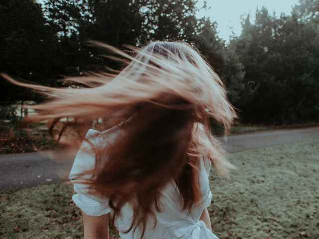 woman with flying hair in summer park