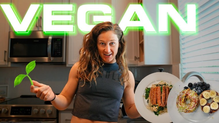 """Tia-Clair Toomey goes vegan for a day. Photo says """"vegan"""" with Tia in the kitchen showing vegan food and a young plant."""