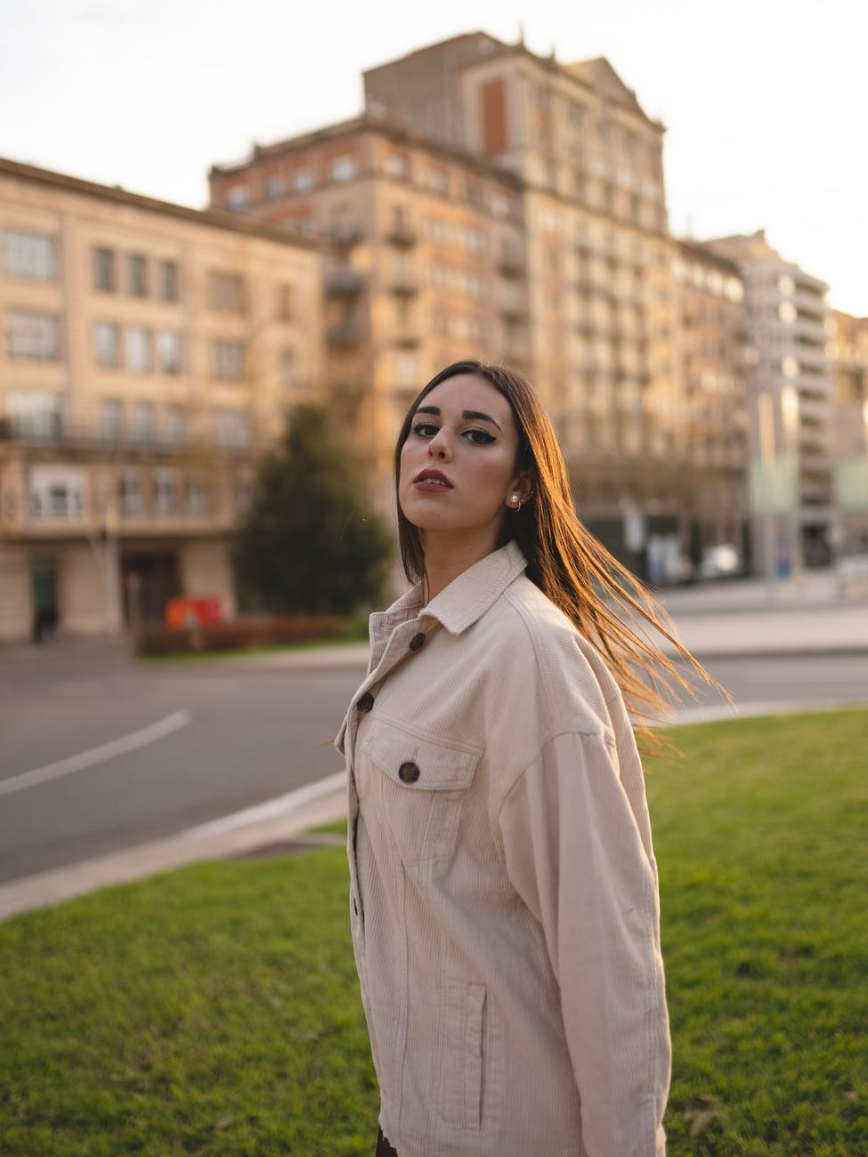 stylish young serious woman standing on city street at sunset