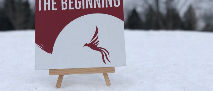 "Photo of a canvas sign that says ""This is just the beginning"" with a red phoenix in the bottom. The background is a winter scene."