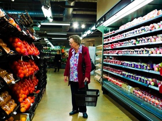 Ältere Frau, die überfordert ist von dem großen Angebot im Supermarkt
