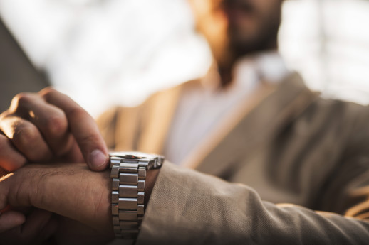Close up of unrecognizable businessman checking the time on his watch.