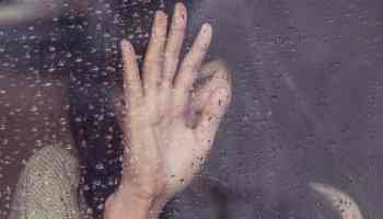 Hand on a window with water on it.