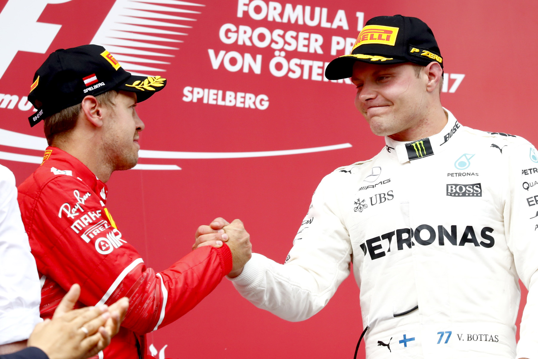 Valtteri Bottas shakes Sebastian Vettel's hand on the Austrian Grand Prix podium.
