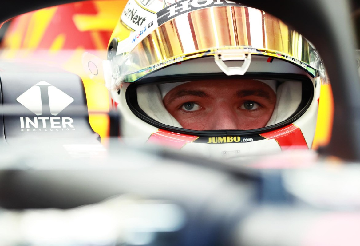 Max Verstappen sits in his car with his visor open