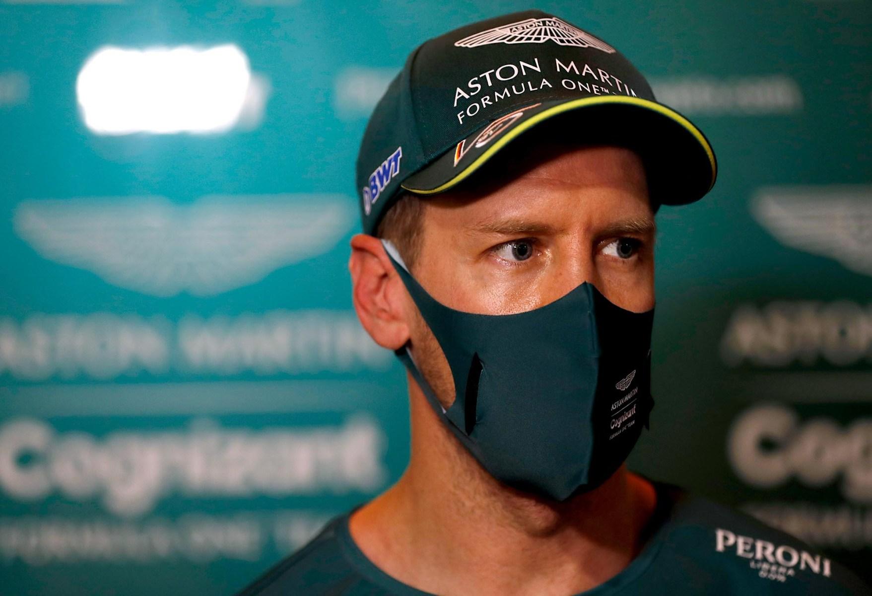 Sebastian Vettel looks on while wearing a mask