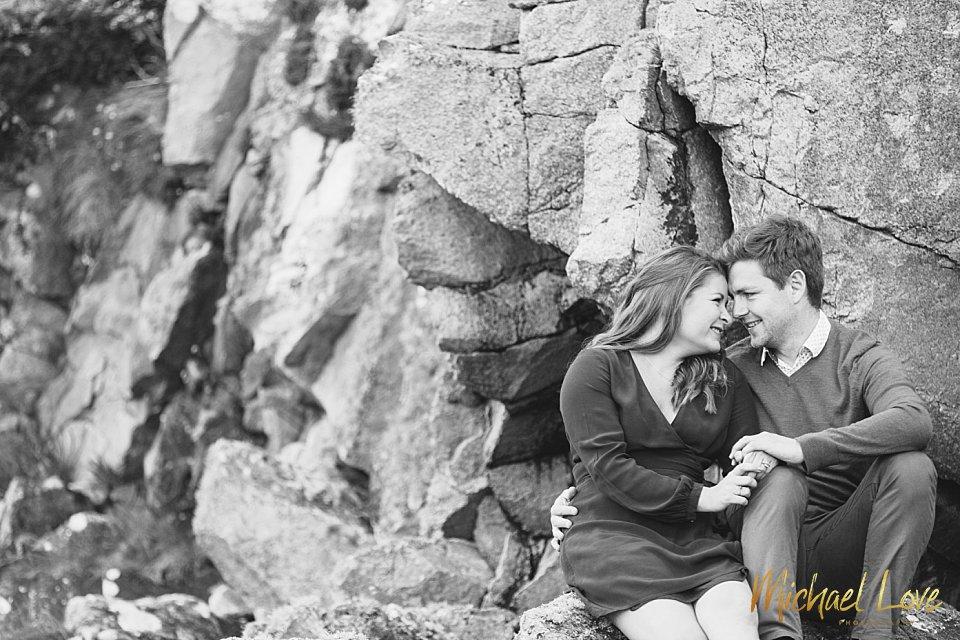 Engaged couple sitting on some rocks