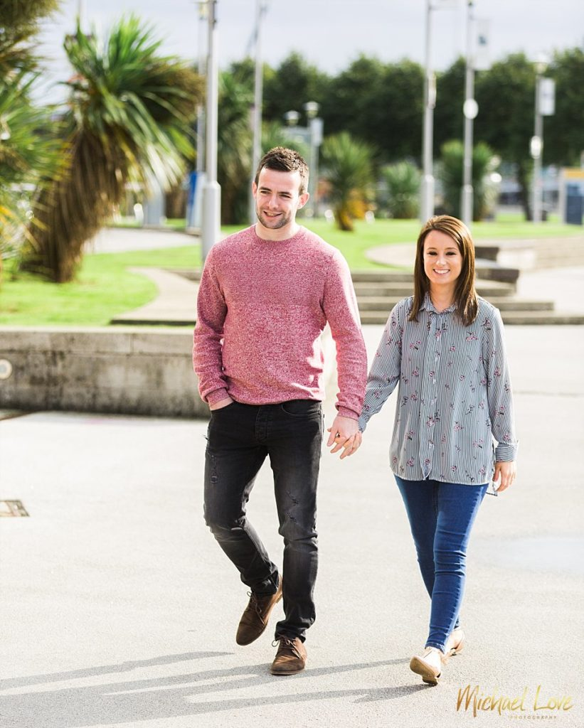 Man and woman walking along the riverfront in Belfast