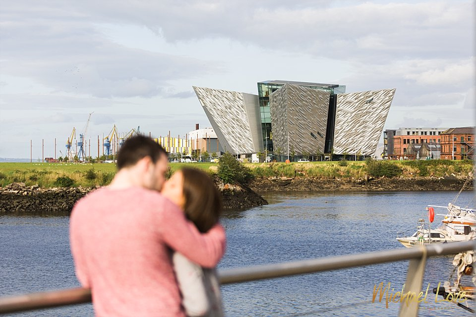 Engaged couple kissing outside the Titanic building in Belfast