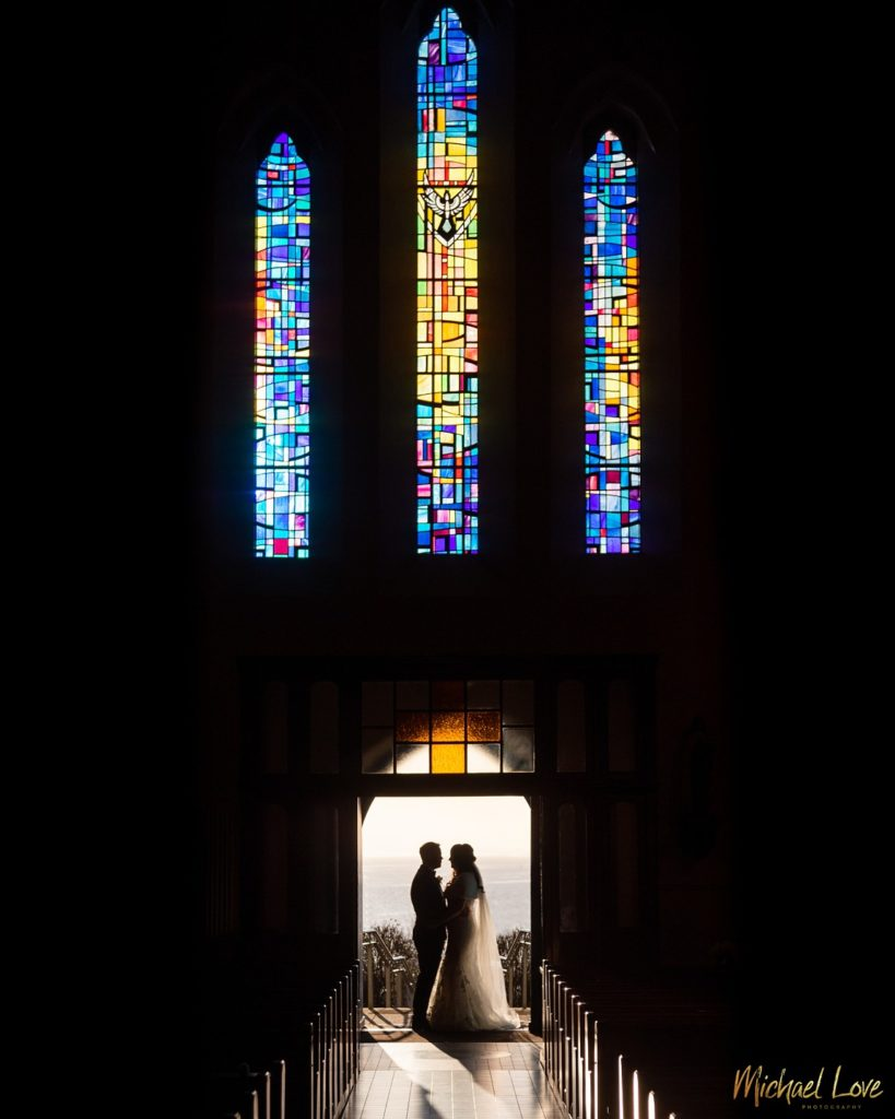 Silhouette of wedding couple underneath church stained glass window