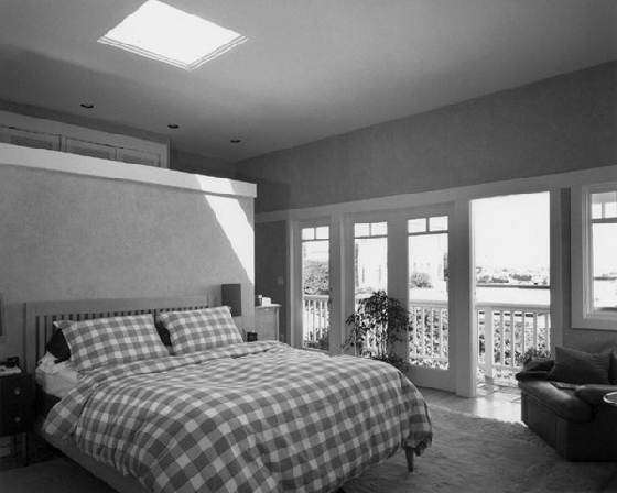 bedroom with large window and balcony