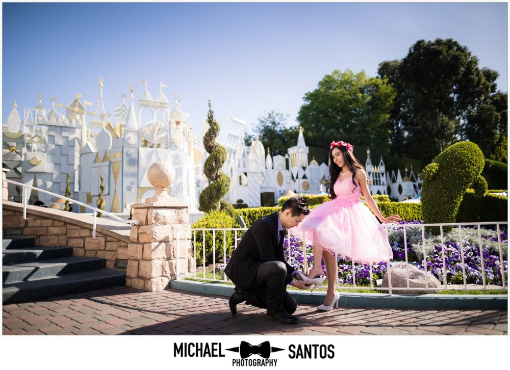 couple in front of its a small world during engagement session at disneyland