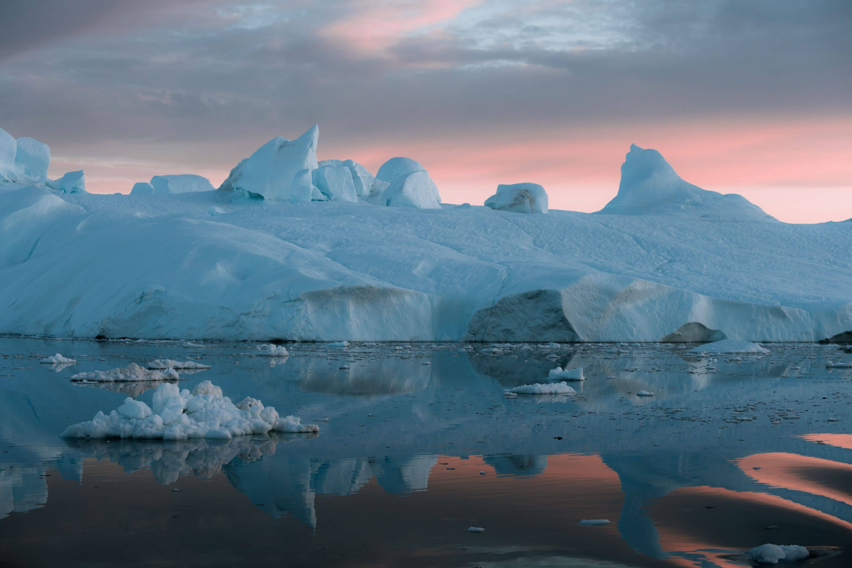 Fine art photographer Michael Schauer captures Icebergs on the coast of Greenland gently being lit by an arctic sunset creating a colour similar to Panone's living coral colour of the year 2019