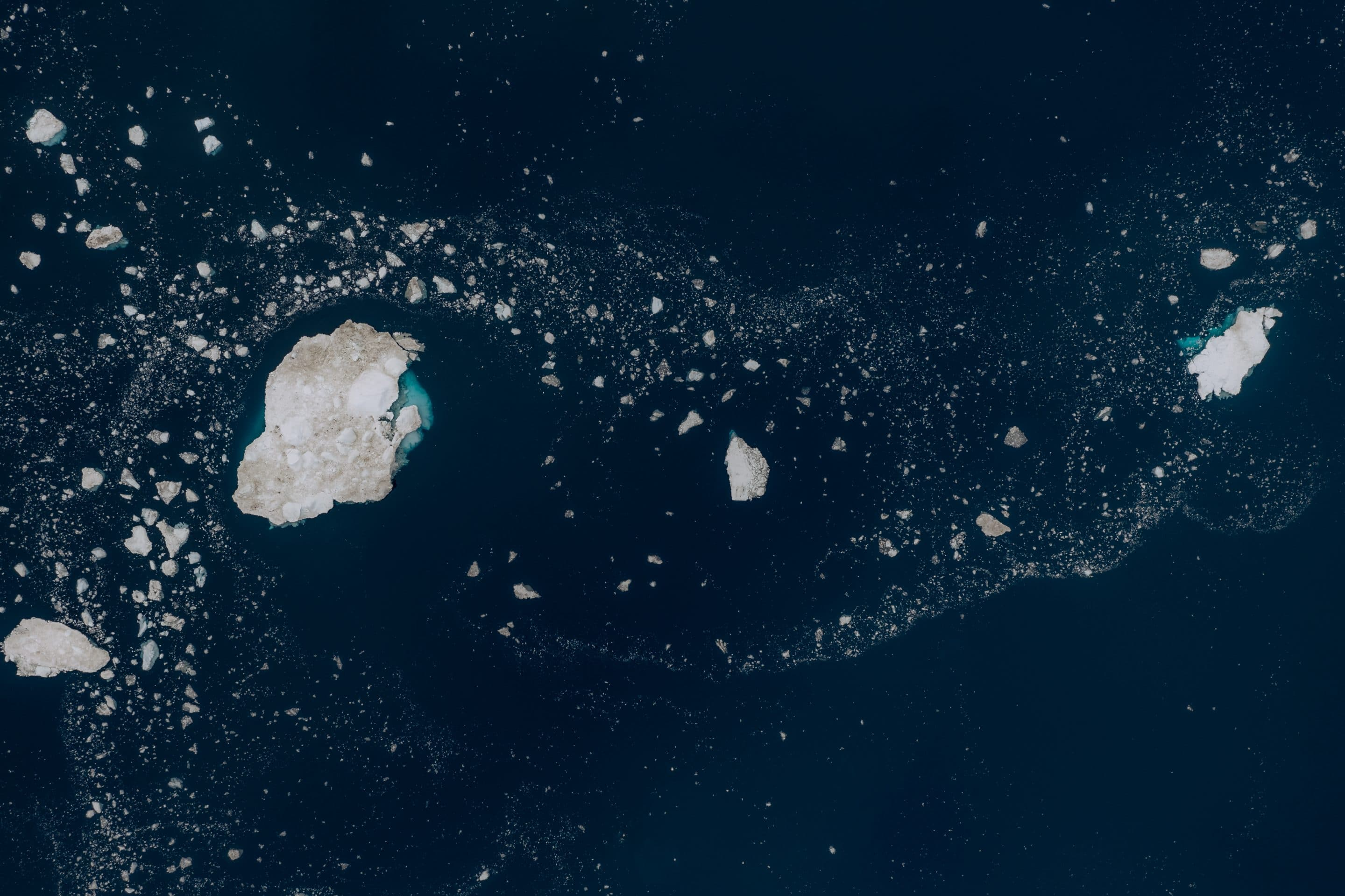 Fine art aerial photography series that sees the sea ice in Greenland as stars and galaxies that are forming a universe in the calm Atlantic ocean by Michael Schauer