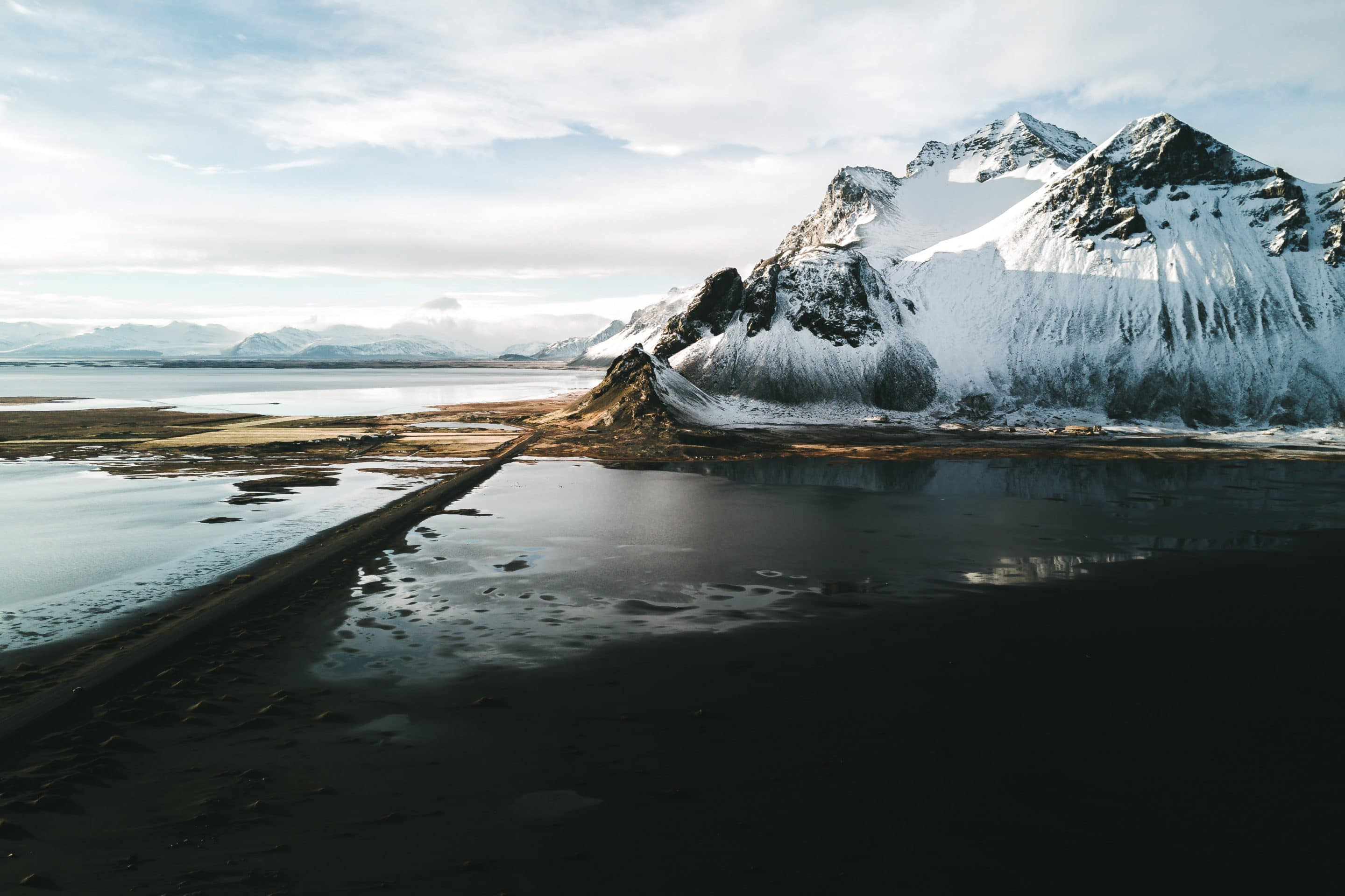 The Stokksnes peninsula in Iceland during a sunset dipping the mountain and beach landscape in moody light by photographer Michael Schauer