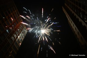 Fireworks overheard between buildings illuminating the night sky
