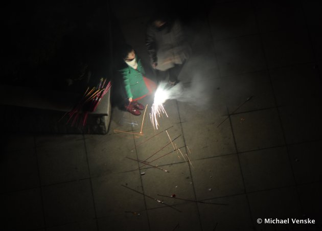 Looking down on mother and daughter illuminated by ignited sparkler