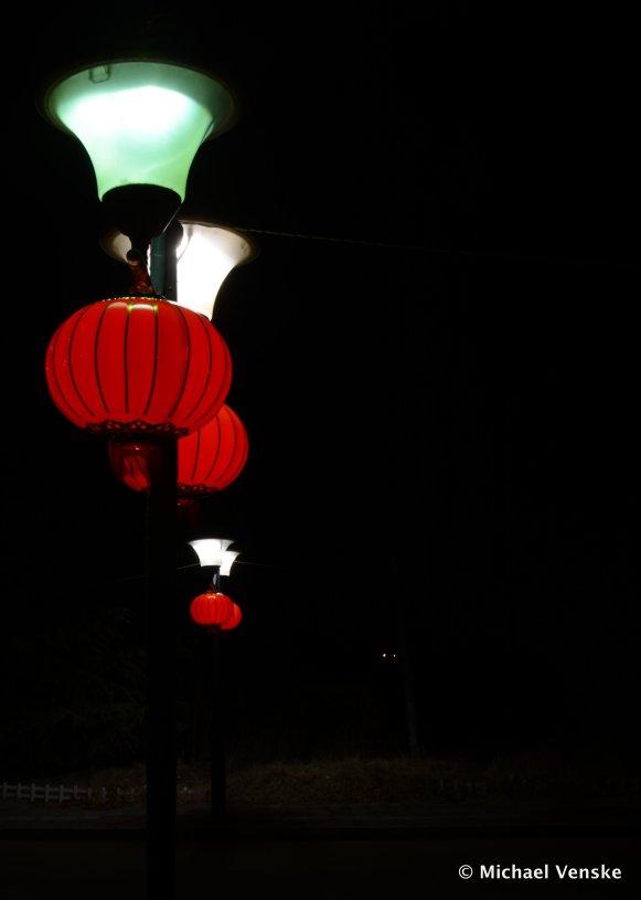 Red Chinese lanterns hanging on street lamps at night