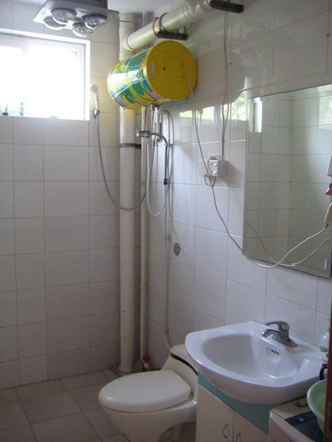 The yellow tank near the ceiling is a water heater. In addition to a western toilet, shower and sink, there is a small washing machine just out of frame to the right of the sink.