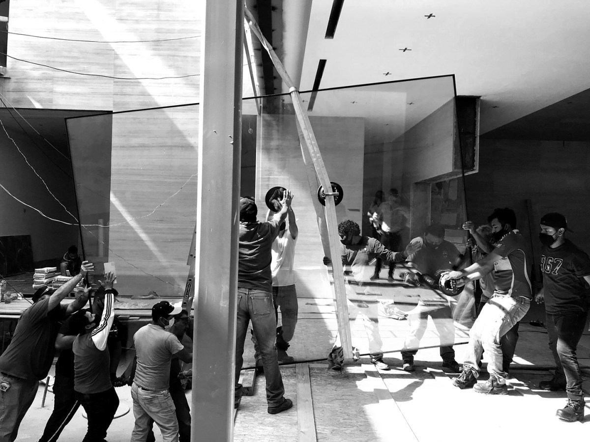 Monterrey Design R+D Adventures: How many guys does it take to install an oversized glazing panel?   Teamwork gets the job done!