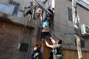 Soime Free Syrian Army drag a dead man out a building recently invest  by them,in Damas.
