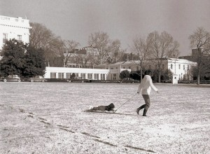 Hiver 1962 - Après une légère chute de neige, la première dame Jacqueline Kennedy traite John Jr. pour une balade en traîneau sur la pelouse de la Maison Blanche.