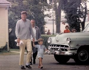 Été 1963 - Le président Kennedy sort d'un magasin de bonbons avec John Jr. en portant son animal jouet.