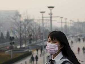 Une jeune femme porte un masque le 19 décembre 2015 à Beijing, en Chine.