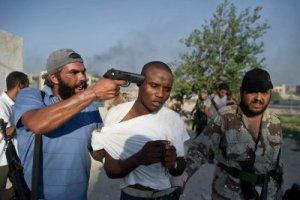 Voici la nouvelle démocratie exportée par les États-Unis en Lybie.Dans quelques secondes après la prise de cette photo,l'homme qui a le pistolet sur la tempe ,mourra...Pour la gloire des terroristes et du 1% qui contrôle les richesses du monde.