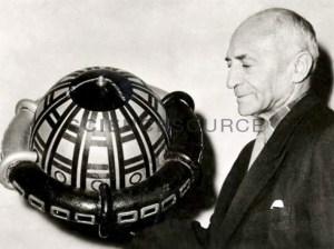Rudolf Nebel (1894-1978), pionnier de la fusée allemande, tenant une station spatiale modèle en 1955. Il avait élaboré ce projet avant la guerre,mais il était en avance sur son temps.Par contre il attira l'attention du Führer.Neber était un membre du groupe de fusée amateur influent de l'Allemagne, le VfR, dans les années 1930. Il a travaillé aux côtés, entre autres, de Hermann Oberth. Il a rejeté l'utilisation de roquettes dans la guerre, en choisissant de ne pas travailler sous Werner von Braun dans le développement de la fusée nazie V2. Après la Seconde Guerre mondiale, son encouragement et ses conférences publiques ont conduit au recommencement de la recherche allemande sur les fusées.