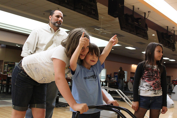 Day 159  Bowling  We're taking advantage of the kids bowl free deal at AMF this summer.  Here's everyone watching Ian's ball zoom down the alley.  I'm amazed with how well I was able to expose all 23 photos I took in the low light of the bowling alley.  I must be getting the hang of it!  Yay!!!  As for the composition of this one, I like the angle. 27mm  Manual  ISO1600  f/4  1/80