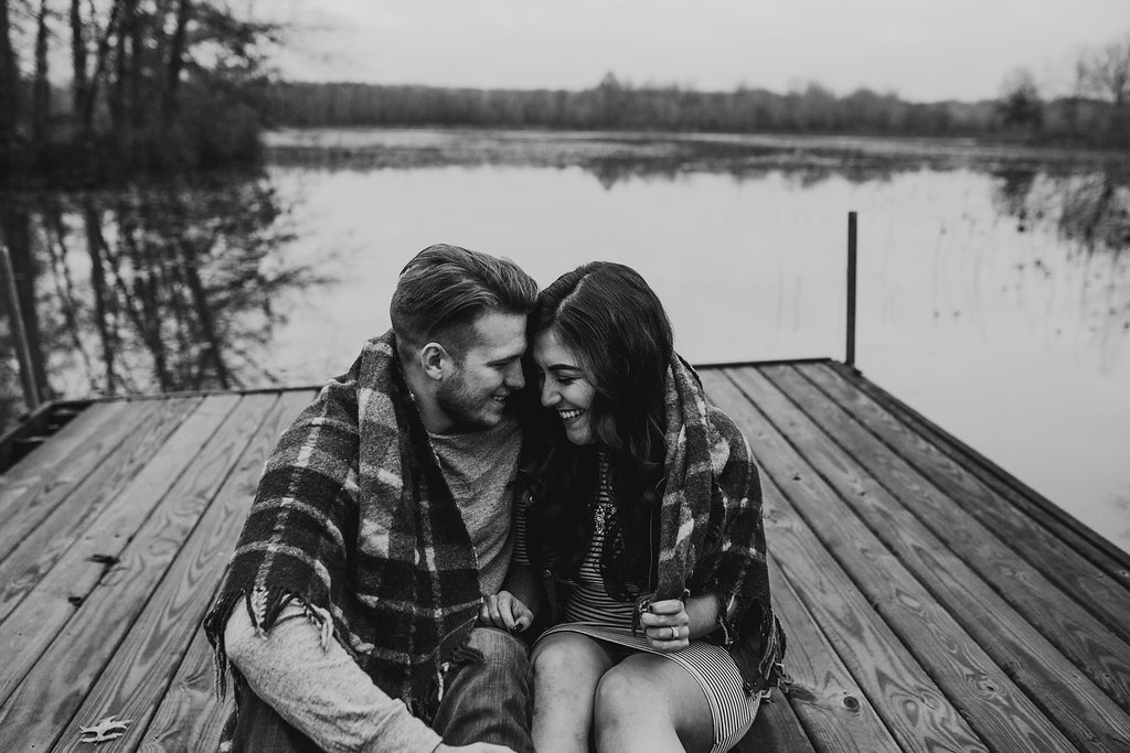 A lake engagement photo of a couple leaning in close, sharing a laugh while wrapped in a blanket, on a dock
