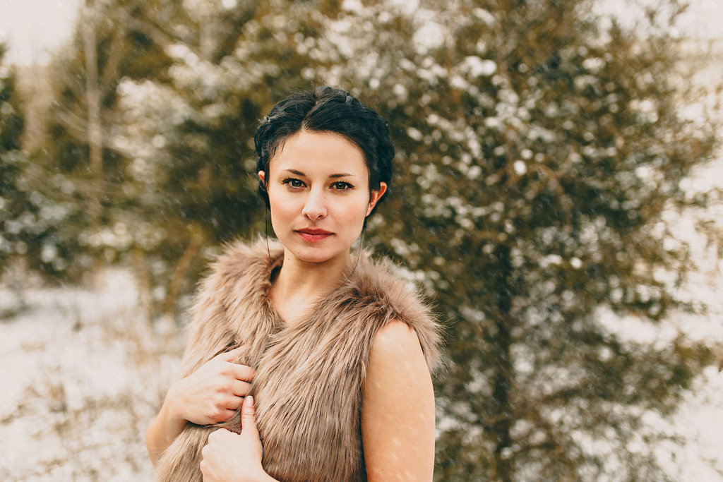 A snow portrait of a woman wearing a fur vest against a wintery forest background.
