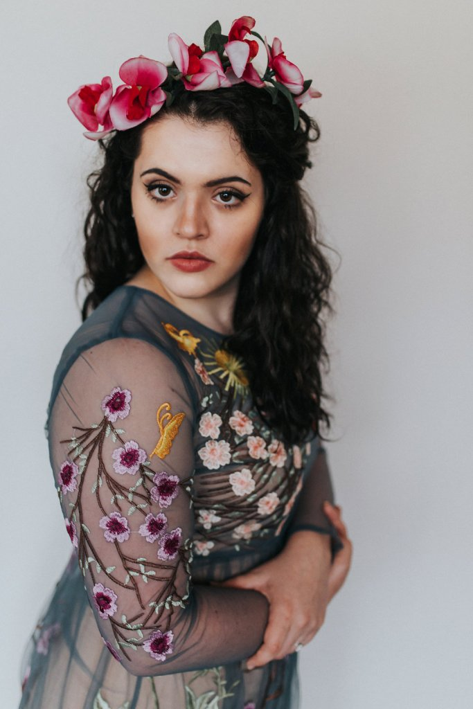 A photo of a girl wearing a flower crown made of orchids. The girl is wearing a sheer blue dress with florals embroidered all over the entire thing.
