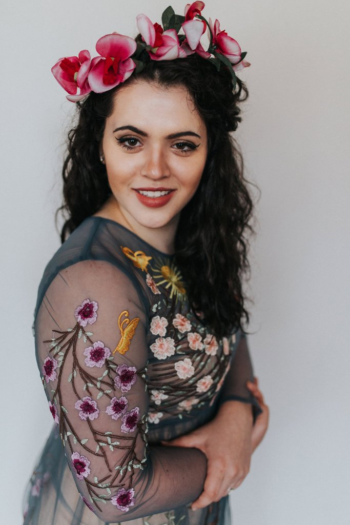 A photo of a girl wearing a flower crown made of orchids. The girl is wearing a sheer blue dress with florals embroidered all over the entire thing..