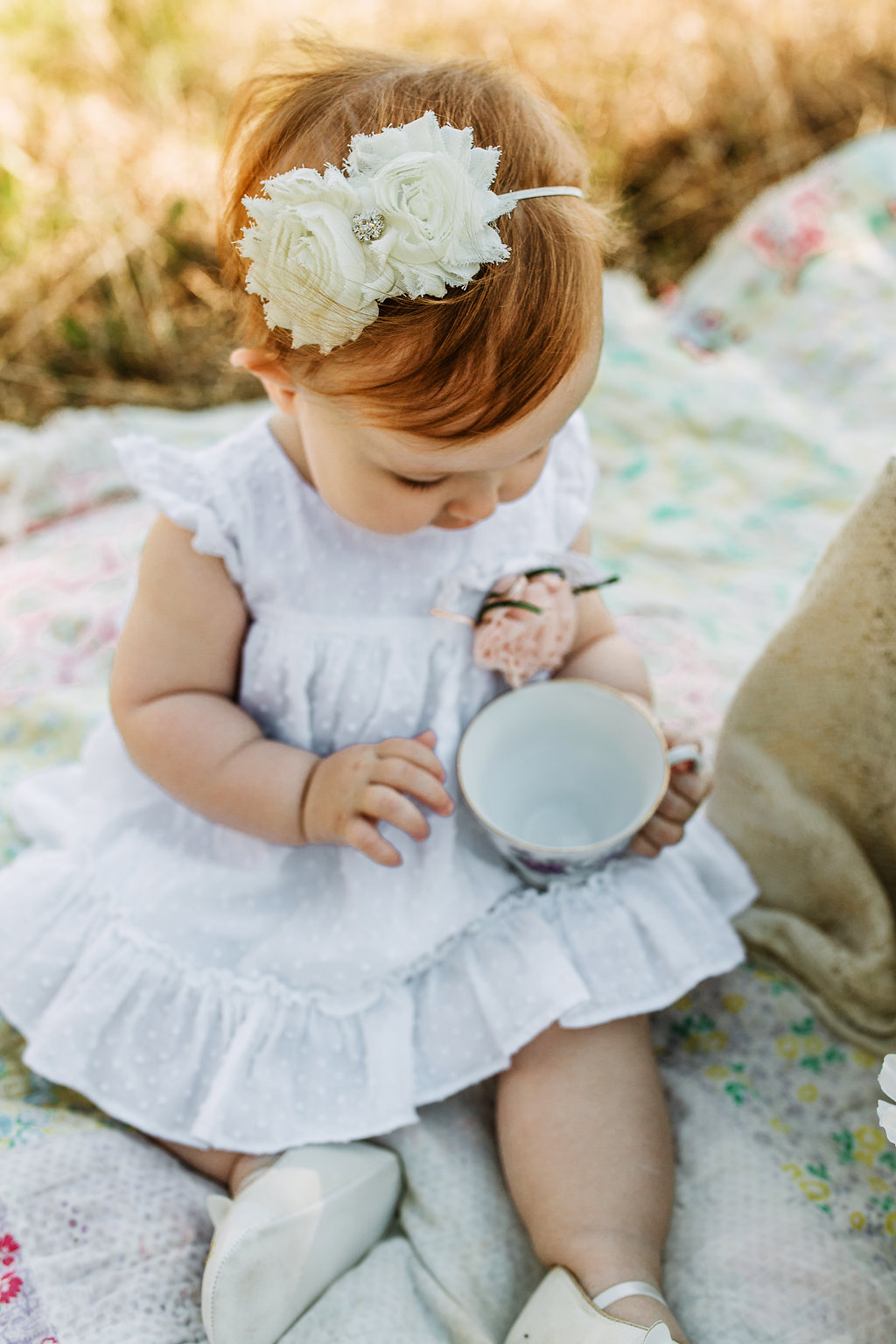 Baby-Holding-Teacup-First-Year