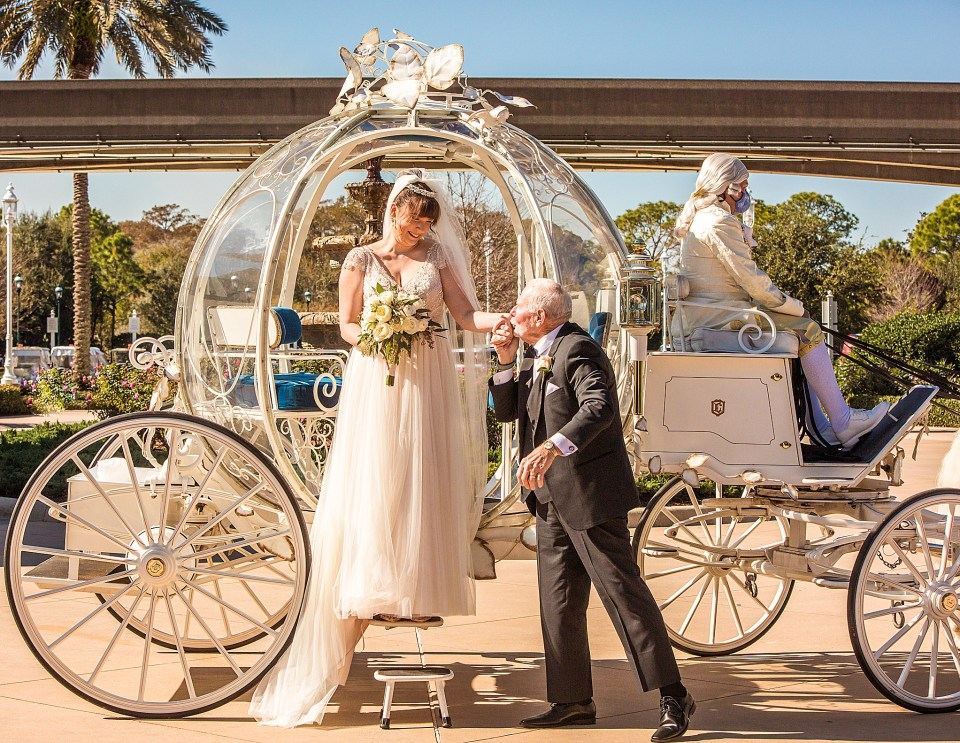 grandfather kissing brides hand as she exits Cinderellas Carriage at Disney Wedding Pavillion