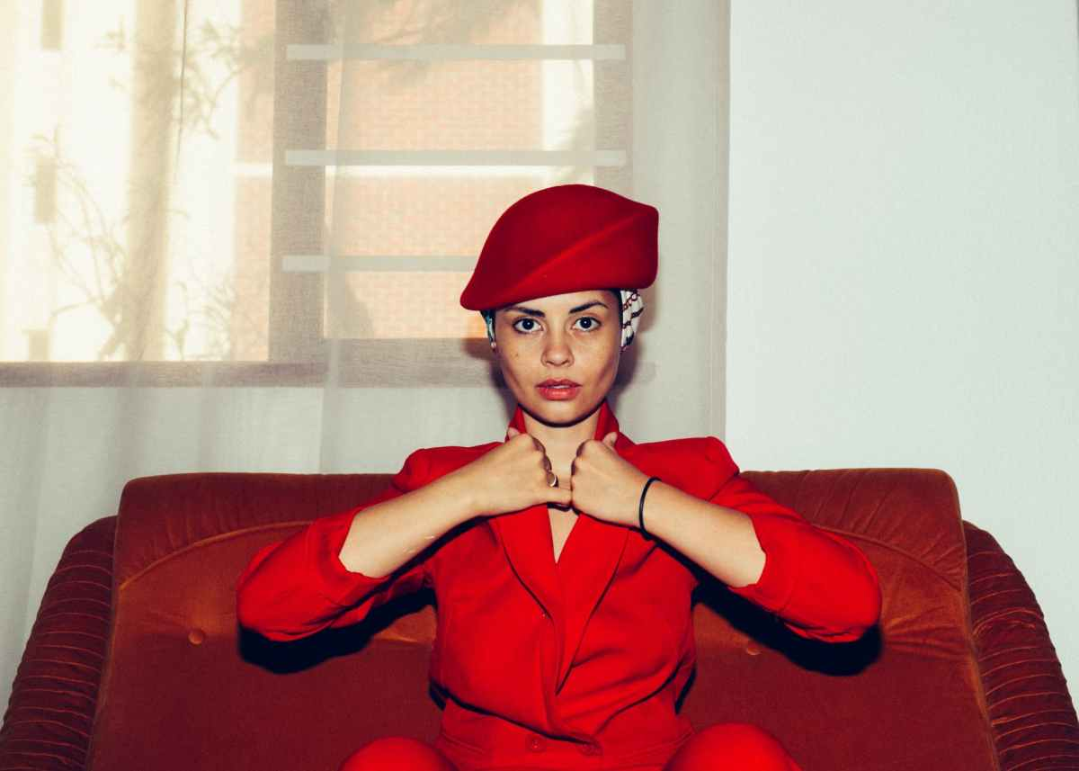 photo of woman in red coat sitting on red sofa