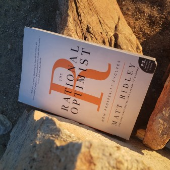 The Rational Optimist book cover on the rocks.