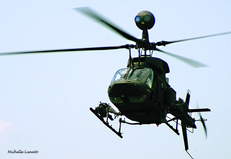 A OH-58D Kiowa Warrior zooms across the sky securing the area for the UH-60 Blackhawks to come in.
