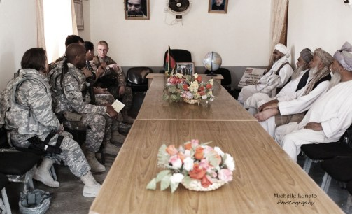 Soldiers and village leaders meet before the donations are given out.